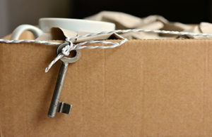 Umzugskarton gefüllt mit Geschirr und einem befestigten Schlüssel